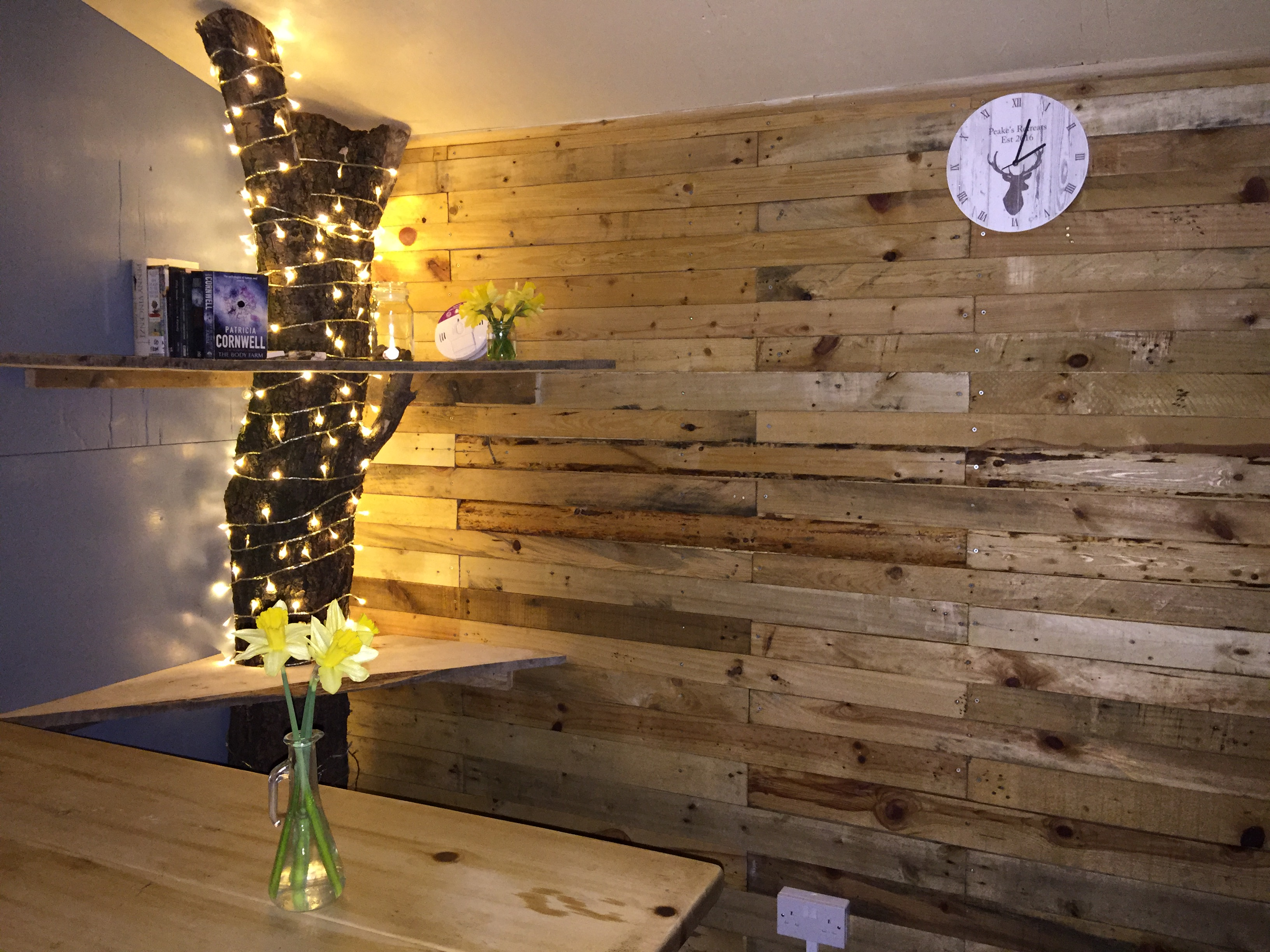 Twinkly fairy lights, spring daffodils, a tree trunk shelf and our wood clad wall all add to the design of our glamping cooking cabin
